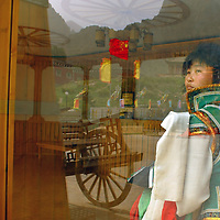 A Mongolian girl look trough the window at the Mongolian Female restaurant in the Buddhist region of Bayan Hot, far west to China at inner Mongolia Autonomous Region. Aug-28-2006/ Photo Stringer