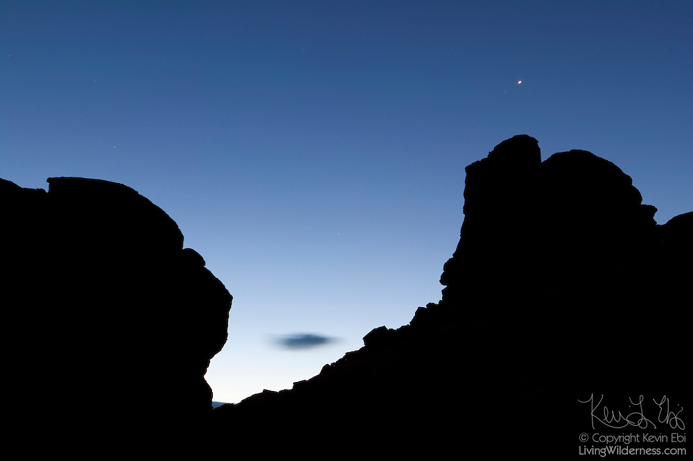 A bright star shines over the dramatic rock formations in the Valley of Fire, Nevada, rendered as silhouettes in this early morning view.
