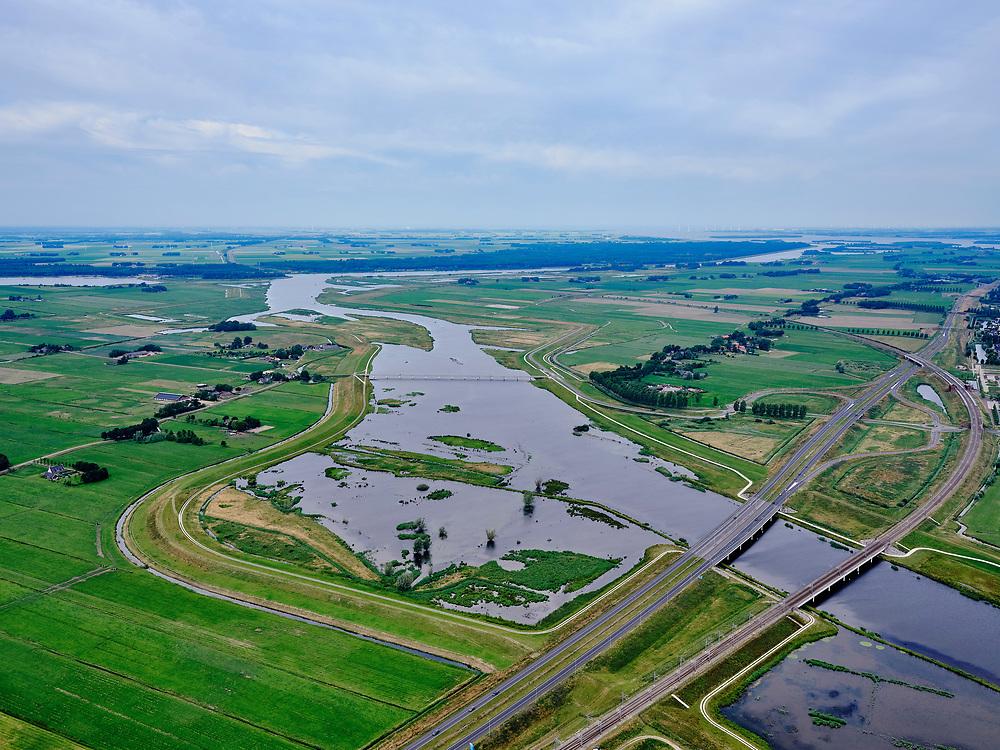 """Nederland, Overijssel, Gemeente Kampen; 21–06-2020; het Reevediep richting monding in het Revemeer (voorheen Drontermeer) met in de voorgrond Spoorbrug Reevediep en Reevediepbrug(rijksweg N50) en natuurgebied De Enk. Midden de Nieuwendijkbrug, Flevoland en Ketelmeer aan de verre horizon.<br /> Het Reevediep is aangelegd in het kader van het project Ruimte voor de Rivier om bij hoogwater water af te voeren voordat dit het nabij gelegen Kampen bereikt, direct naar het IJsselmeer, de 'bypass Kampen'. Het Reevediepgebied is ook een natuurgebied en vormt een ecologische verbindingszone tussen rivier de IJssel en Drontermeer.<br /> Reevediep towards the outfall in the Revemeer (formerly Drontermeer). In the foreground the Reevediep Bridge (national road N50) and the Reevediep Railway Bridge, Flevoland on the far horizon.<br /> The Reevediep has been constructed as part of the Room for the River project, and functions to discharge high waters before reaching the nearby Kampen, directly to the IJsselmeer, the """"bypass Kampen"""". The Reevediep area is also a nature reserve and forms an ecological connecting zone between the river IJssel and Drontermeer.<br /> <br /> luchtfoto (toeslag op standard tarieven);<br /> aerial photo (additional fee required)<br /> copyright © 2020 foto/photo Siebe Swart"""