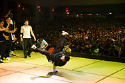 A dancer standing on one hand performing on stage in front of a big crowd of audience. UK B-Boy championships 06. 08/10/2006