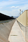 A culvert runs along the international border wall between Agua Prieta, Sonora, Mexico, and Douglas Arizona, USA, as seen from Arizona.