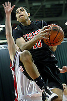 JEROME A. POLLOS/Press..Post Falls High's Shawn Reid elevates in front of a Madison High defender after getting a fast break in the second half of their game Friday during the state 5A boys basketball tournament at the Idaho Center in Nampa.