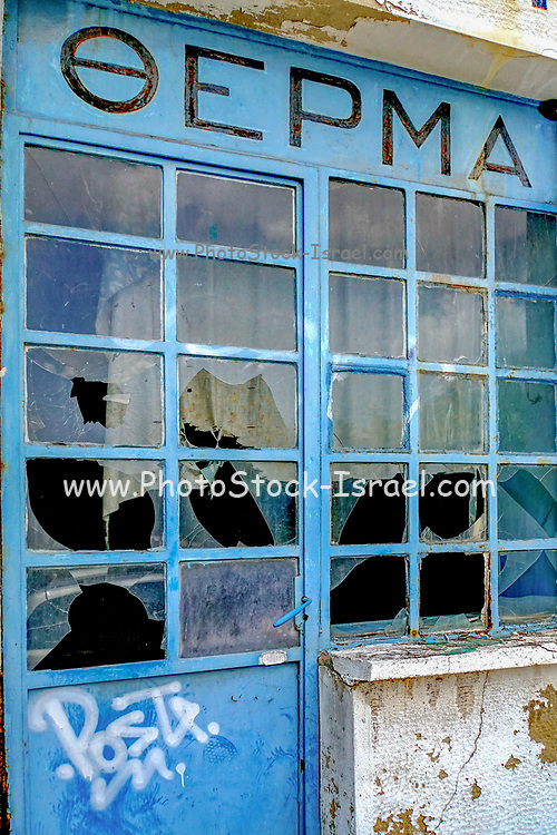 Deserted and dilapidated store front with broken window panes. Economic hardship and depression. Photographed in Athens, Greece