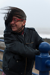 © Licensed to London News Pictures. 8/02/2016. Porthcawl, Bridgend, Wales, UK. Rickie from Cwmbran in Wales visits Porthcawl for Storm Imogen. People struggle to stay on their feet in winds gusting over approximately 60mph. Storm Imogen batters the small Welsh seaside resort of Porthcawl in the county borough of Bridgend on the South coast of Wales, UK. Photo credit: Graham M. Lawrence/LNP