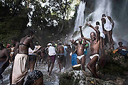 Every year thousands of devotees seek fortune in the goddess Erzulie<br /> <br /> At 150 kilometers from Port au Prince, Haiti's capital, a waterfall flows. Thousands of pilgrims come to the place where they say appeared Erzulie, the goddess of love and beauty then camouflaged in the Virgin of Miracles. The offering becomes a ritual show in search of fortune in the poorest country of America, beaten in 2010 by earthquakes, disease and misery.<br /> <br /> Every year, thousands of pilgrims who have saved recent months to afford the cost of travel-the waterfall is 150 kilometers north of Puerto Principe move there, walk for hours to the waterfall and allowed to bathe in its waters. Bodies, songs and the most common in voodoo celebrations, weird music mixed with scents of herbs and potions prepared to ask favors from the spirits. Believers spend hours in the sound and the freshness of the water, praying, hugging. Many throw their old clothes to the sky, a symbol of a past they want to leave behind. And some consult their hougan (priests) or mambo (priestess), owned by the loas (voodoo deities. Thousands of faithful, including children and pregnant women huddle under a waterfall for the bathroom of luck and invoked the . Ezili Ewa figure, one of the main characters of the voodoo pantheon Under the waterspout is impossible to hear a word, the devotees dance, make ablution with bottles and bowls of pumpkin and delivered to communion with saints 'praise'. These are baroque and colonial names as Baron Samedi, Brigitte Maman, Papa Legba, Damballa and Papa Ogou.<br /> According to popular legend, in 1847 Erzulie Dantor, voodoo goddess of beauty and love, appeared on a tree, in this cascade, and began to heal the sick and perform miracles. Catholic priests saw this as blasphemy and ordered to cut down the trunk, erecting a few meters from a church in honor of the Virgin. By Haitian art work and syncretism, Erzulie is camouflaged in the Catholic Our Lady of Miracles. Since then, many of the inhabitants of t