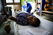 "Drifting in and out of consciousness, 34 year old Kumbini Brand is given intravenous fluids at the screening and admission section of a Cholera Treatment Centre in Harare...Children and adults are treated at Beatrice Road Infectious Diseases Clinic in Harare, Zimbabwe...The clinic is staffed by locals but assisted by MSF. As of 30 May 2009, there were 98 424 suspected cases, including 4 276 deaths reported by the Ministry of Health and Child Welfare (MoHCW) of Zimbabwe since August 2008. Fifty-five out of 62 districts in all 10 provinces were affected. in December 2008, Robert Mugabe declared that ""there is no cholera"" in Zimbabwe. Failing sanitation and lack of water supply were to blame, workers responsible claimed they had not been paid by the government for several months."