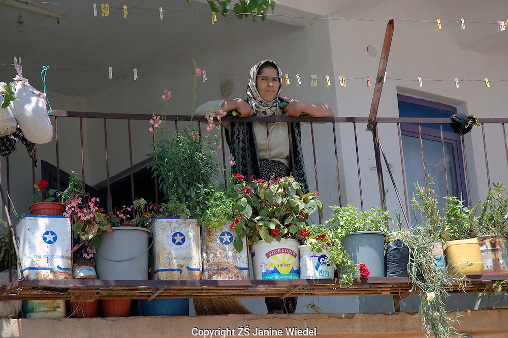 Woman standing on balcony with plants growing in old olive oil tins in Turkish village.