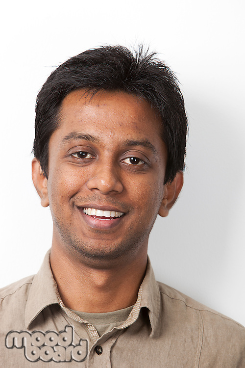 Portrait of young Indian man smiling against white background
