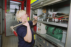 Part time female firefighter placing equipment in fire engine compartment,