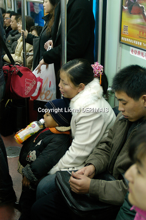 Chinese woman with young child in the Beijing subway..December 2005
