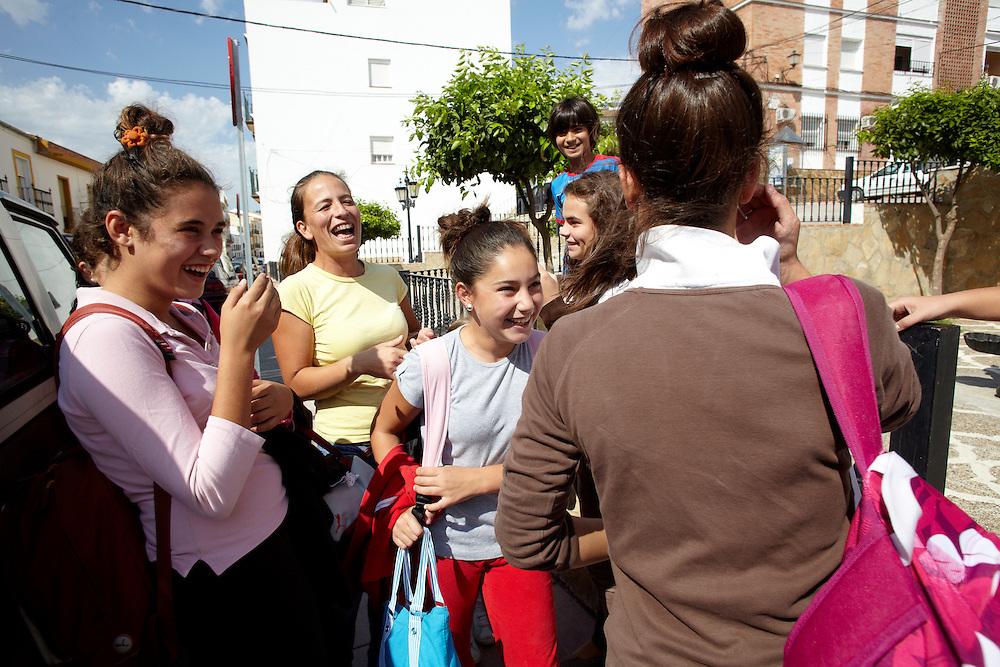 """07/10/10. ALCALÁ DEL VALLE (CADIZ).  Muchas parejas jóvenes viven separadas de sus hijos mientras trabajan en el sur de Francia. Los niños viven con parientes directos que no emigran, normalmente abuelos o tíos, y la distancia no es fácil para nadie. Uno de los momentos más emotivos del año en Alcalá del Valle se produce el día en que los temporeros llegan al pueblo. Las madres irrumpen en la escuela y los pequeños se lanzan a sus brazos en un gesto impulsivo que provoca las lágrimas de todos los presentes. Hay muchos temas de los que hablar y durante días las madres viven con intensidad el reencuentro con sus hijos. La familia de Ana y Antonio """"el """"Rejano"""" se reencuentra a la salida del instituto..FOTOGRAFIA: TONI VILCHES."""