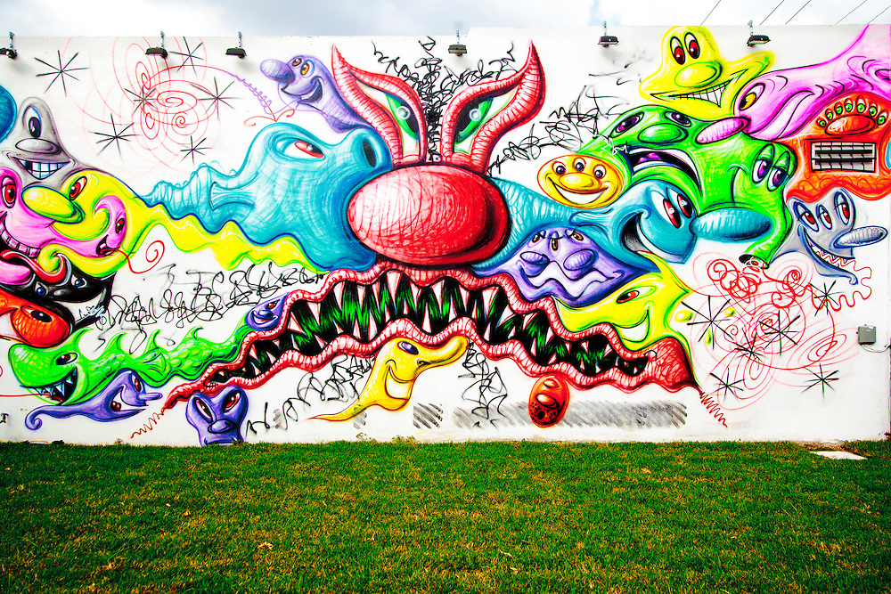 Curated street art mural painted by pop-artist Kenny Scharf is one of the major works at The Wynwood Walls outdoor mural gallery in Miami's Wynwood arts district.