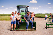 "06 AUGUST 2020 - FAIRFIELD, IOWA: GARY ADAM (center, sitting on tractor bucket) watches the bidding during the auction on his farm near Fairfield. Adam, 72 years old, has been farming in the Fairfield area since 1971. He decided to retire this year because he wants to travel and because it's so difficult to make money in farming this year. He said he wants to ""shed the risk and responsibility. If things were super good, like they were 2006-2012, I might stay in it, but they're not."" An increasing number of farmers in the Midwest are retiring this year as it becomes harder to make money on crops. In addition to low prices, Iowa farmers are being hit with a drought this year, with well below average rain over most of the state. Because of the COVID-19 pandemic, the auction on Adam's farm was one of the first live in person auctions since winter. Most auctions are now done on line.     PHOTO BY JACK KURTZ"