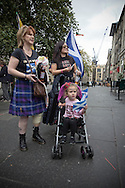 A young girl in a buggy on the Royal Mile prior to the start of a pro-Independence march and rally in the Scottish capital. The event, which was staged in support of the pro-Independence movement, was attended by an estimated by approximately 30,000 people. The referendum to decide whether Scotland will become an independent nation will be staged on 18th September 2014.
