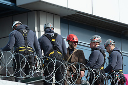 © Licensed to London News Pictures. 10/10/2019. London, UK. An Extinction Rebellion protester is removed from the roof of the main entrance to London City Airport by police officers in specialist climbing equipment. Photo credit: Peter Manning/LNP