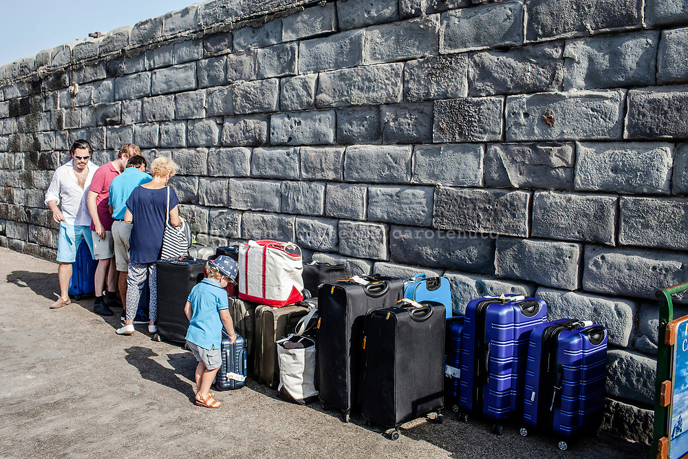 04 August 2017, Capri Italy - tourists prepares luggage on the pier before the arrival of ferry-boat.