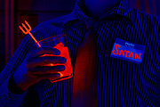 A man with a Satan name tag holds a glowing cocktail with a pitchfork stirstick. Blacklight photography.