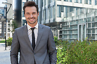 Portrait of smiling young businessman standing against office building