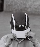 A young kid pulls his BMX cap over his face, Southall, UK, 1987.