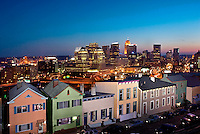 Twilight photograph of Downtown Cincinnati with brightly lit row houses in Mount Adams in the foreground