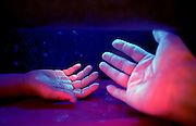 The hands of 7-year-old Lucas Drew, left, and volunteer Jeannie McKinley glow a white phosphorescence under a black light during a demonstration on how easily bacteria is spread between people, photographed at the New Mexico State Fair in Albuquerque, N.M., Friday, Sept. 22, 2000. Participants are given a special hand lotion that imitates bacteria. Fluorescent lamps highlight the lotion as if it were bacteria. The volunteers then wash their hands normally and check for bacteria under the fluorescent light again. (AP Photo/Pat Vasquez-Cunningham)