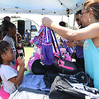 "LIBBY EZELL | BUY AT PHOTOS.DJOURNAL.COM<br /> Aleika Hunt, 9 recieves her backpack full of school supplies from volunteer Valerie Fields Saturday at the Jackson's 5k ""Run to Stop the Violence and Fun Day at Verona City Park"