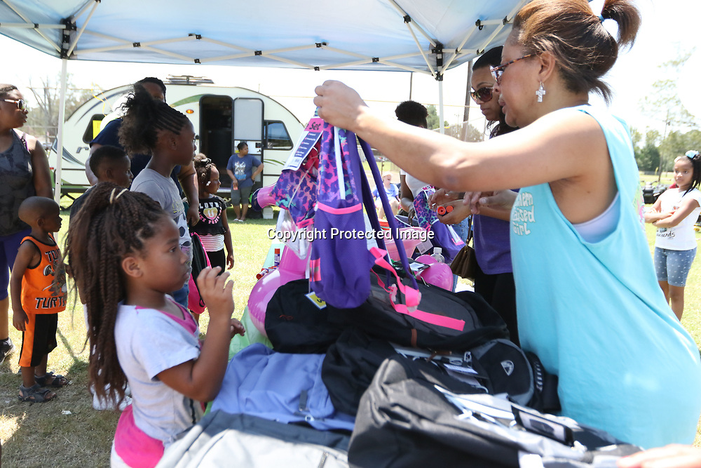 LIBBY EZELL | BUY AT PHOTOS.DJOURNAL.COM<br /> Aleika Hunt, 9 recieves her backpack full of school supplies from volunteer Valerie Fields Saturday at the Jackson's 5k &quot;Run to Stop the Violence and Fun Day at Verona City Park