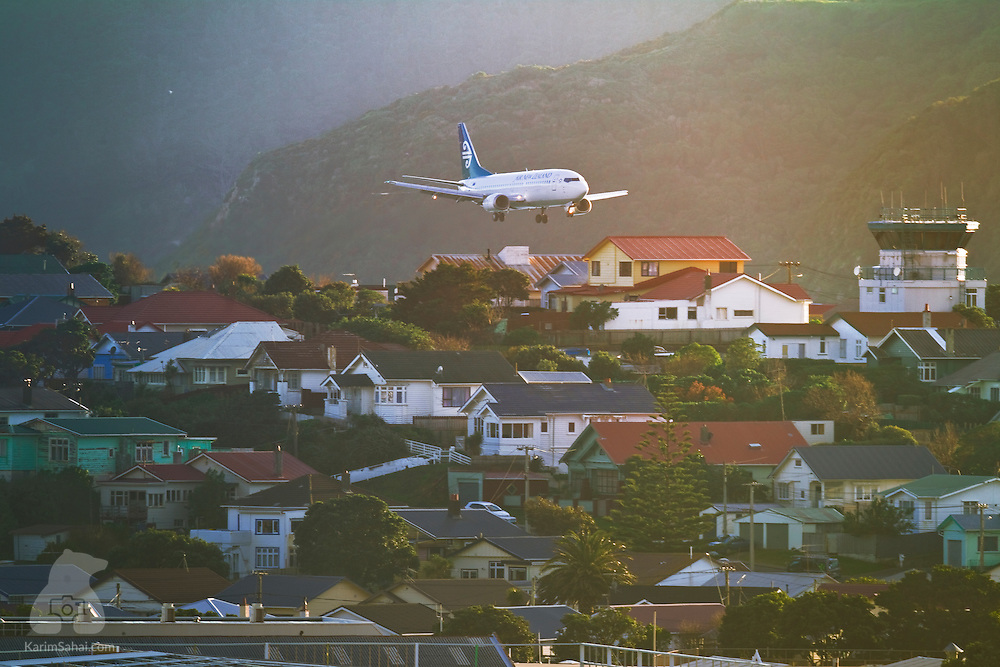 An Air New Zealand aircraft flies above a residential neighborhood prior to landing at the Wellington International Airport, New Zealand.