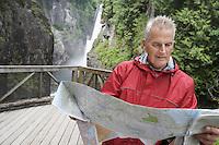 Senior man reading map waterfall in background