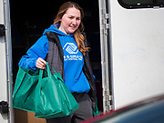 """17 MARCH 2020 - DES MOINES, IOWA: SARAH MERCER-SMITH, with the Boys & Girls Clubs and working with the Des Moines Area Religious Council (DMARC), brings bags of food to a family in the parking lot of Carver Elementary School in Des Moines after giving bags of food to a family. Des Moines Public Schools are closed for at least 30 days because of the Coronavirus outbreak. Des Moines area religious organizations and food banks are working together to bring free food to children in at risk communities. Volunteers and workers are practicing """"social distancing"""" by leaving the food packages on the pavement and recipients pick up the packages. Tuesday, the Governor of Iowa ordered all restaurants and bars to close or go to take out only. The Iowa Department of Public Health has urged all public buildings, like libraries and schools, to close, and all schools in Iowa are closed for at least 30 days.     PHOTO BY JACK KURTZ"""