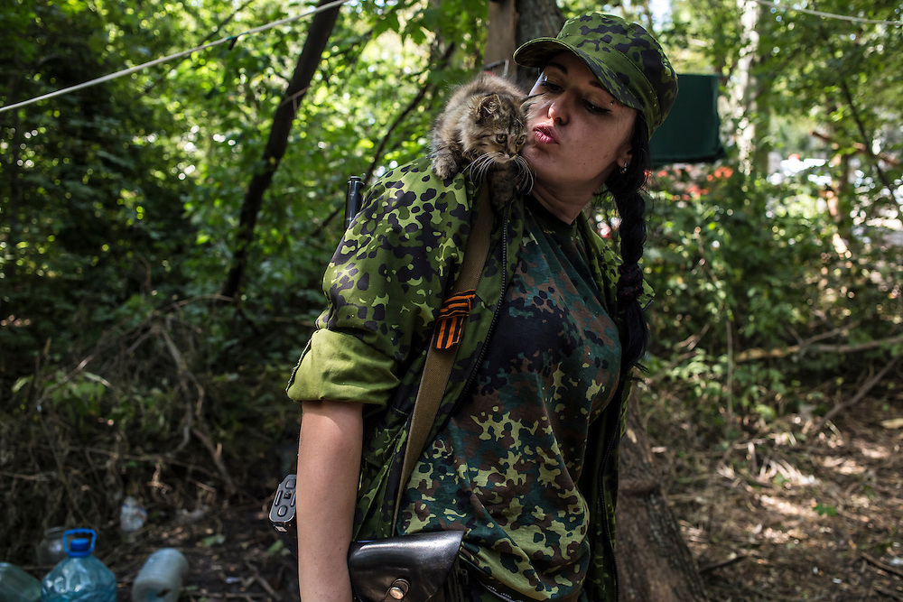 Marta, a pro-Russia rebel, with a kitten at a camp by a checkpoint on the outskirts of the city on Monday, July 28, 2014 in Horlivka, Ukraine.