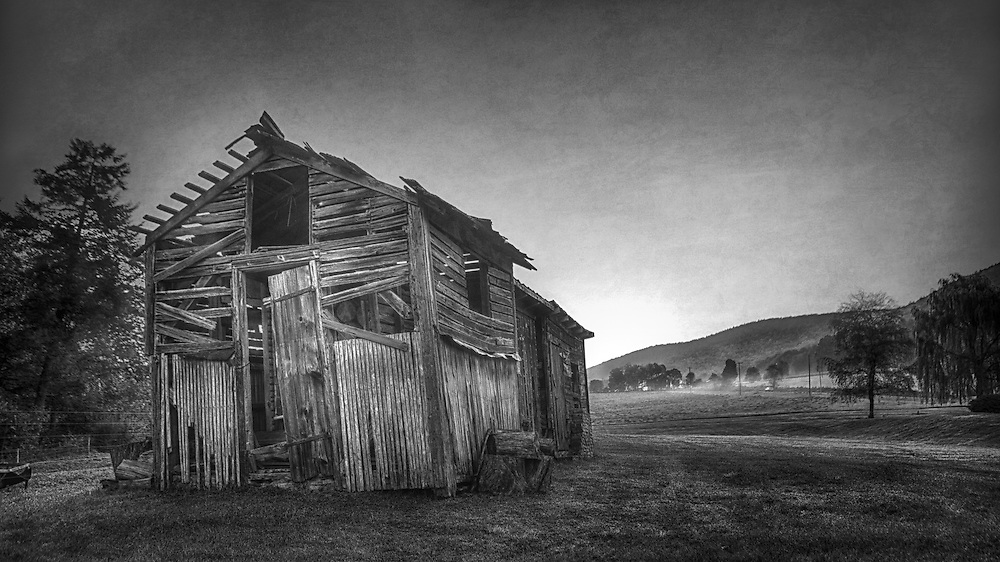 A black and white photo of an old shed set on a beautiful farm landscape in Loganton, PA
