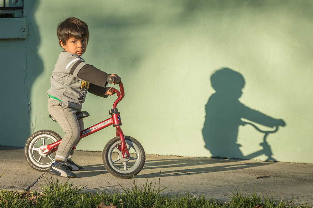 Two year old Leonel Vargas rides his balance bicycle at the Green Church at third and Washington Streets in Calistoga.