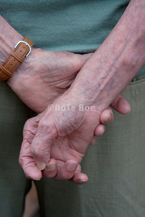 close up of the hands clasped behind the back of an elderly person