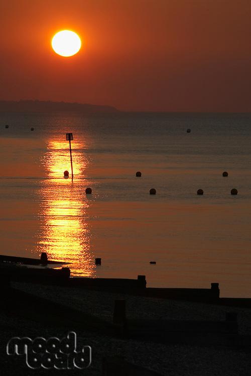 Sun setting over sea and breakwaters on beach