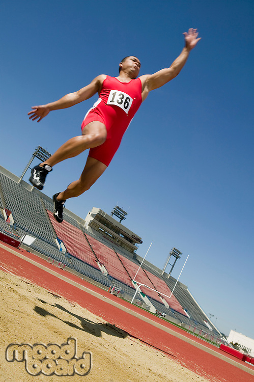 Male athlete long jumping, mid-air
