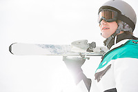Smiling young man carrying skis against clear sky