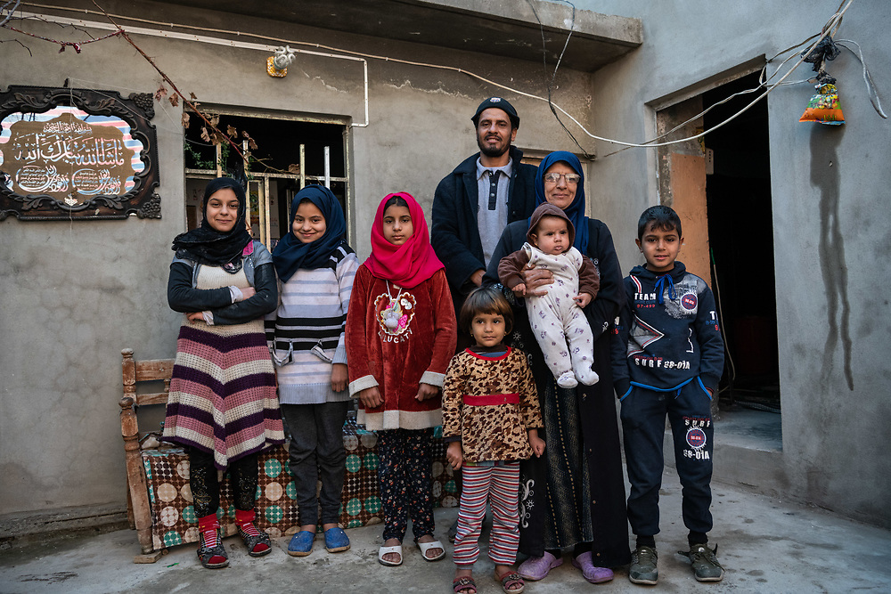 4 February 2019 – Mosul – Iraq – Mother of two, Rahbia Dahesh Huseein, 50, stands for a photo with her family inside her home in West Mosul, which was damaged as a result of a nearby airstrike during the battle to liberate Mosul from ISIS control.  <br /> <br /> Rahbia's home is now being rehabilitated with the support of UNDP's Funding Facility for Stabilization (FFS), which is supporting the rehabilitation of ten thousand homes across West Mosul, helping displaced families return home. <br /> <br /> © UNDP Iraq / Claire Thomas