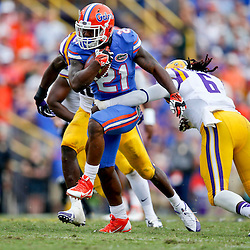 Oct 12, 2013; Baton Rouge, LA, USA; Florida Gators running back Kelvin Taylor (21) breaks a tackle by LSU Tigers safety Craig Loston (6) during the second half of a game at Tiger Stadium. LSU defeated Florida 17-6. Mandatory Credit: Derick E. Hingle-USA TODAY Sports