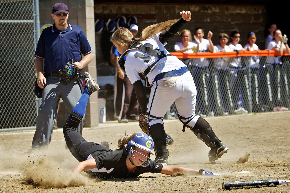 Coeur d'Alene High's Kyeli Parker slides under and around the glove of Timberline High catcher Kendra Nagy as she tags home plate Friday in the State 5A tournament at Post Falls High.