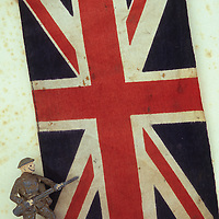Marked and stained Union Jack flag lying on antique paper with worn lead model of World War 2 army foot soldier with rifle