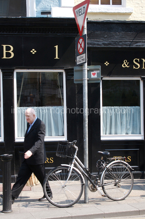 Man walking past bar in Dublin Ireland, bicycle locked to Yield sign