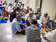 26 JULY 2013 - BANGKOK, THAILAND:  Men eat the Iftar meal at Haroon Mosque in Bangkok. Iftar is the Muslim meal that breaks the day long fast during Ramadan. Ramadan is the ninth month of the Islamic calendar, and the month in which Muslims believe the Quran was revealed. The month is spent by Muslims fasting during the daylight hours from dawn to sunset. Fasting during the month of Ramadan is one of the Five Pillars of Islam. Muslims believe that the Quran was sent down during this month, thus being prepared for gradual revelation by Jibraeel (Gabriel) to the prophet Muhammad.       PHOTO BY JACK KURTZ
