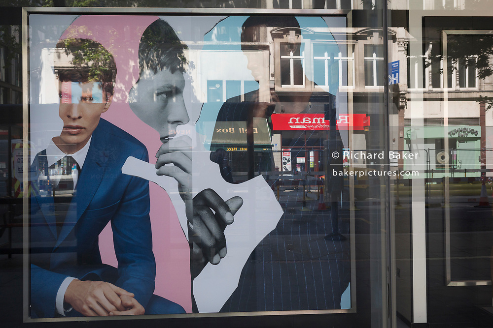 As the UK's Coronavirus death toll during the government's social distancing lockdown, rose by 384 to 33,998, and the R rate of infection is reported to be between 0.7 and 1.0, the faces of male models are seen in the window of a clothing business in a deserted City of London, the capital's financial district, on 15th May 2020, in London, England.