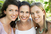 Three women in garden smiling portrait close-up