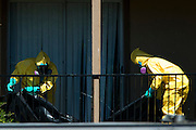 A haz-mat crew prepares to enter the Ivy Apartments where Thomas E. Duncan, the first confirmed Ebola virus patient in the United States, was staying with family in Dallas, Texas on October 3, 2014. Duncan is now being treated at Texas Health Presbyterian Hospital Dallas while members of his family have been isolated in the apartment. (Cooper Neill for The New York Times)