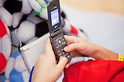 30 DECEMBER 2009 -- PHOENIX, AZ:  Mackenzie Saunders (CQ) uses her cell phone to text a friend from her bed at St. Joseph's Hospital in Phoenix Wednesday. Mackenzie was knocked down by another player during a soccer game. She finished the game but later in the day her legs started hurting and her parents took her to a hospital. Three hospitals later, she was in St. Joseph's with a diagnosis of a swollen spine and she couldn't walk. Now she's in physical therapy. She is expected to make a full recovery but her doctors have said she won't be able to play soccer for at least another 16 months.  Photo by Jack Kurtz