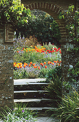 Looking through the arch into the barn garden at Great Dixter in spring. Tulipa 'Prinses Irene' in the foreground.
