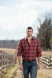 rugged masculine man in a plaid shirt on a ranch