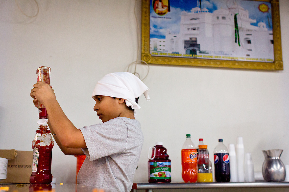 A Sikh boy helps prepare the Sunday meal, open to the public, at Shri Ravidas Gurudwara.